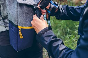 Hiker closing his partner's backpack