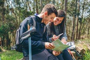 Couple doing trekking sitting lookin