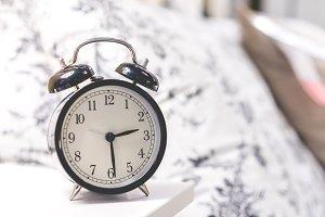 Classic alarm clock on bed