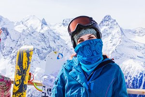 Woman with ski mask and snowboard.