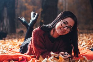 Girl lying on the plaid in autumn fo