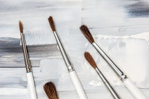 Paint brushes on artistic canvas
