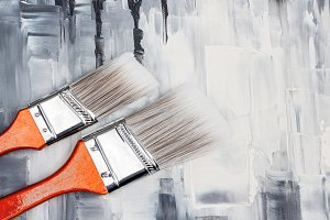 Two paint brushes on artistic canvas