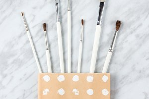 White paint brushes in a paper bag