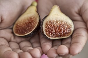 Girl hand holding a Sliced fig