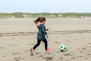 Little girl playing soccer on the be