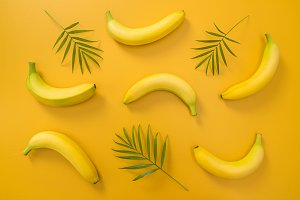 Palm leaves and bananas on yellow bg