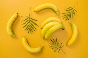 Bananas and palm leaves on yellow bg