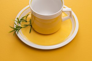 Ceramic teacup on yellow background