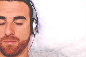 man lying with headphones in bed