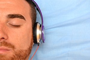 man with headphones lying in bed