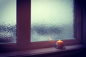 Candle burning near a frosted window