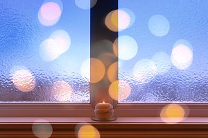 Frosted window, candle and lights