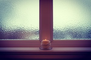 Burning candle and frosted window