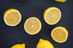 Whole and cut lemons on dark slate