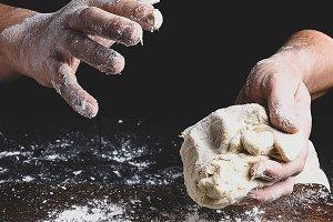 baker kneads white wheat flour dough