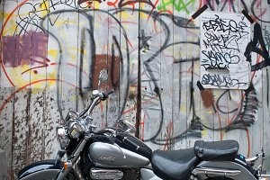Motorbike parked in front of graffit
