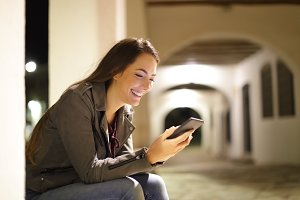 Happy woman using a smart phone sitt