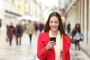 Happy woman walking using a cellphon