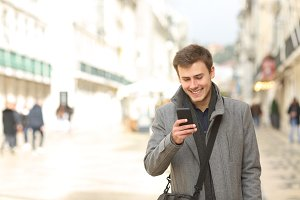 Man walking using a smart phone in w