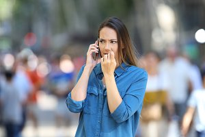 Nervous woman talking on phone on th