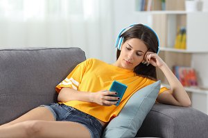 Relaxed girl in yellow listening to