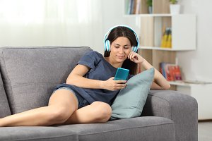 Relaxed teen listening to music lyin