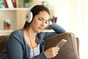 Sad girl wearing headphones listenin