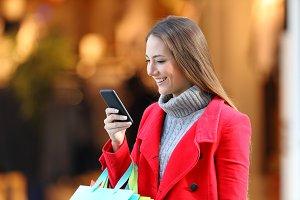 Shopper using a smart phone in a mal