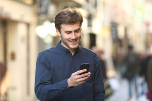 Smiley man checking smart phone cont