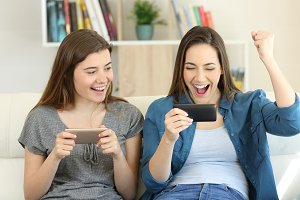 Two excited friends playing games an