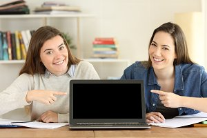 Two students pointing at laptop scre