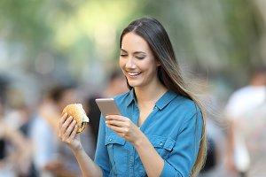Woman holding a burger checking smar