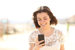 Woman walking checking phone content