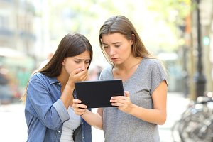 Worried friends reading online news