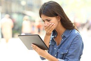 Worried girl reading online news in
