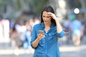 Worried woman checking smart phone m