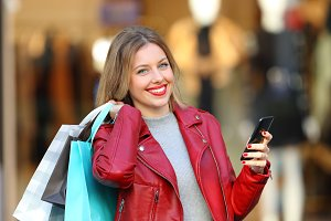 Happy shopper holding bags and phone