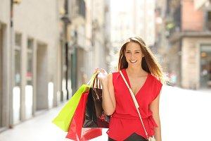 Shopper holding shopping bags walkin
