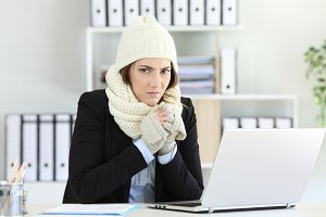Angry businesswoman having cold at o