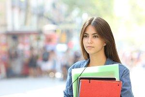 Serious student walking looking away