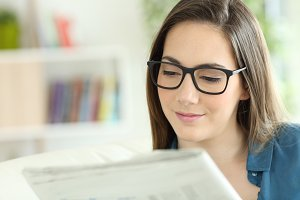 Woman wearing eyeglasses reading a n