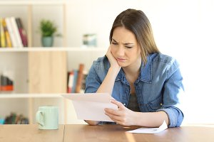 Worried female reading a letter on a