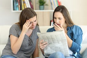 Worried friends reading newspaper ne