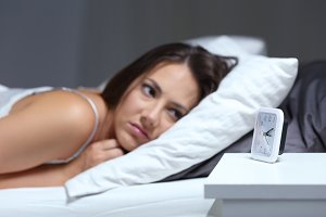 Insomniac woman looking at alarm clo
