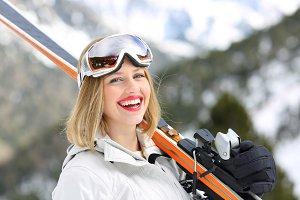 Happy skier looking at camera holdin