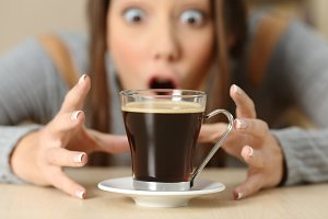 Amazed woman looking at coffee cup