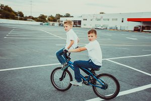 Brothers making tricks riding on one