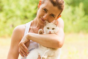 Woman holding white cat in summer