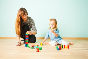 Mother and small daughter building